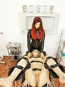 Rubber clinic patient in red latex undressed, and bounded at gyno chair by nurse in black latex