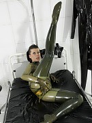 Freaky girl dressing up shiny black rubber clothes in the clinic room