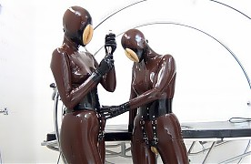 Kinky pussy girls Lena and Samantha, in brown rubber catsuits with integrated perforated masks, rubber pussy masks, rubber corset with garter belts, rubber pussies with buckles, gloves and flat-heel rubber boots, continue with their clinical treatment. To begin, Samantha lies horizontally on the medical bed. While both are grasping heavily for air, Lena caresses Samantha's rubber encased body sensually before climbing on the bed to engage in a 69 position, to perform some muff diving and to sati...