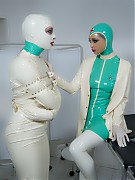 Bondage clinic patient in white latex bondage dress, wearing punishing steel heels